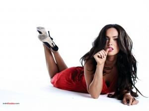 Megan Fox posando tumbada con un vestido rojo