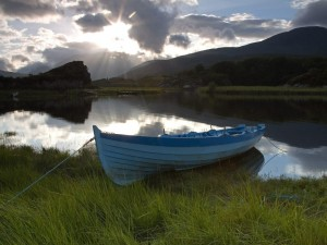 Barca en la orilla de un pequeño lago al atardecer