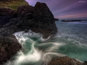 Olas del mar rompiendo contra las rocas