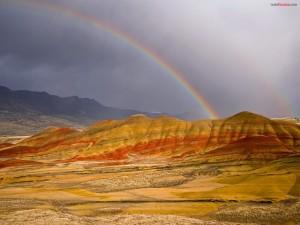 Postal: Arcoíris fundiéndose con la montaña