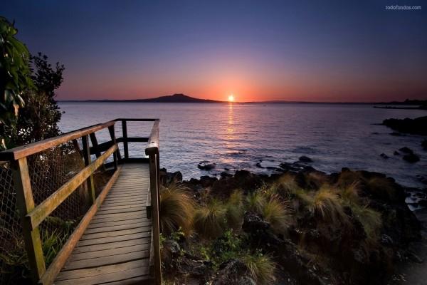 Camino de madera alrededor de la playa, al anochecer