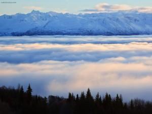 Postal: Montañas nevadas por encima de las nubes