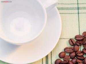Taza vacía y granos de café