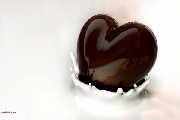 Corazón de chocolate negro sumergiéndose en leche