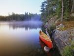 Canoa roja a la orilla de un lago