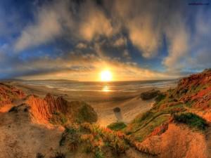 Postal: El Sol despuntando en la playa