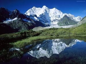 Charca reflejando una montaña nevada