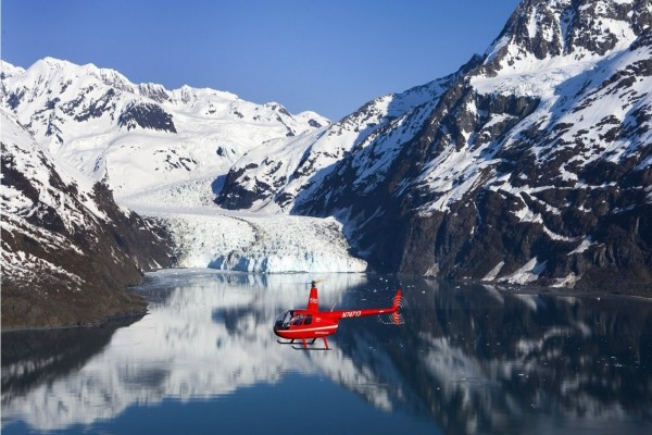 Pequeño helicóptero rojo sobrevolando un lago entre montañas nevadas