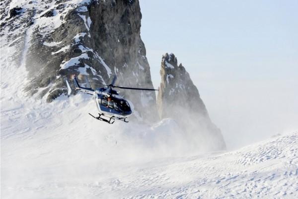 Helicóptero entre montañas nevadas