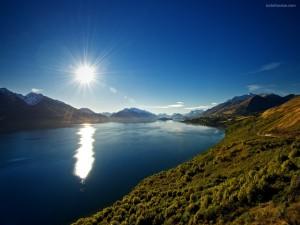 Reflejo de un sol resplandeciente sobre las aguas de un lago