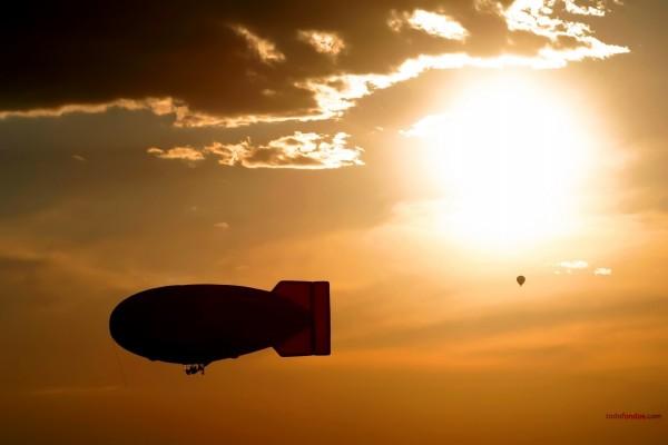Dirigible y globo bajo un cielo dorado