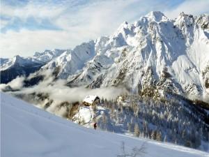 Casita en medio de unas montañas cubiertas de nieve