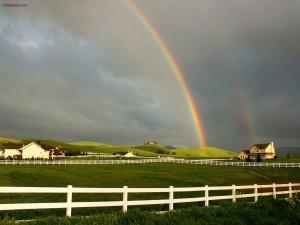 Arcoíris decorando un paisaje de granjas
