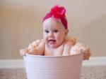 Bebé bañándose en un cubo