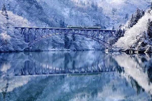 Tren atravesando un puente bajo un paisaje invernal