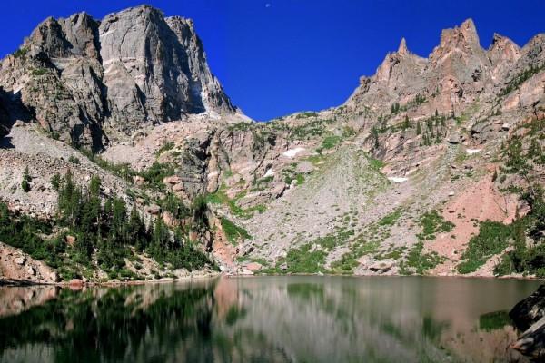 Inmensas rocas que se reflejan en un gran lago con aguas transparentes