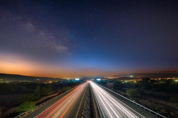 Lineas de luz del tráfico, bajo una noche estrellada