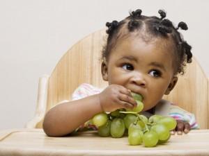 Niña pequeña comiendo uvas blancas