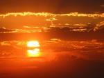 Sol ardiente, en un cielo de nubes