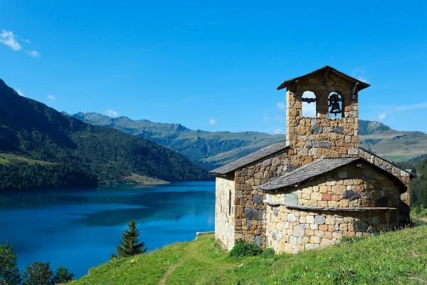 Capilla de piedra junto a un lago azul