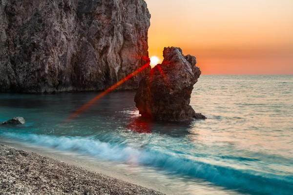 El Sol entre dos rocas, en una playa en la isla de Milo (Grecia)