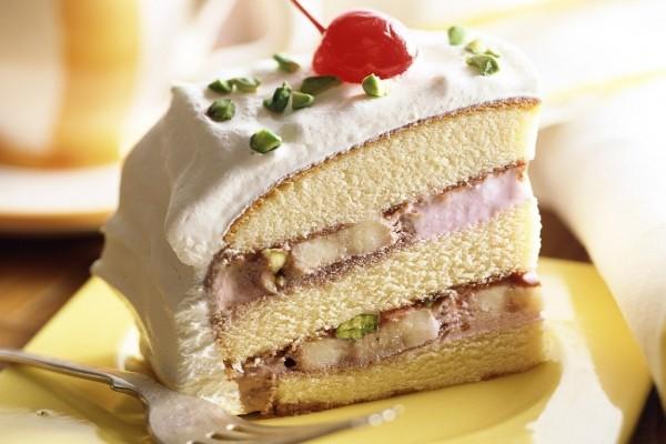 Porción de tarta con nata, pistachos y una guinda
