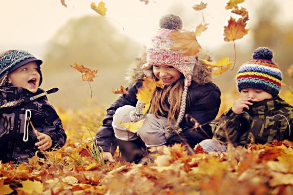 Niños jugando sobre hojas secas