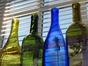 Postal: Botellas de colores con paisajes dentro