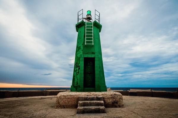Un faro verde en el puerto de Denia, España