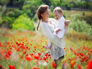 Postal: Madre paseando con su bebé por un campo de amapolas