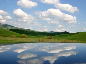Reflejo en el agua de un cielo azul con nubes