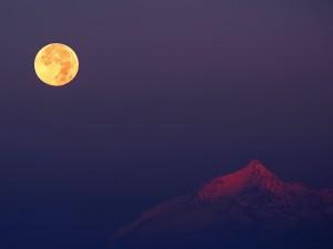 Postal: La luna iluminando la cima de la montaña