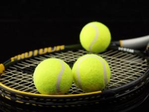 Tres pelotas y una raqueta de tenis