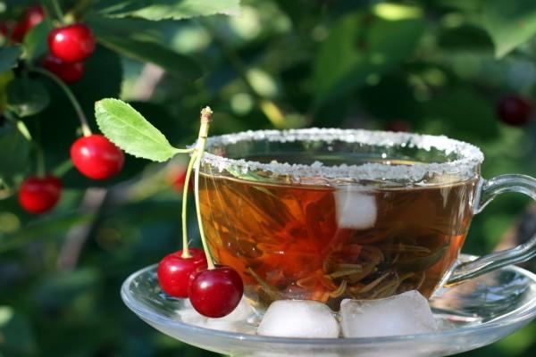 Una taza de té helado con dos cerezas