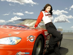 Chica posando sobre un coche de carreras