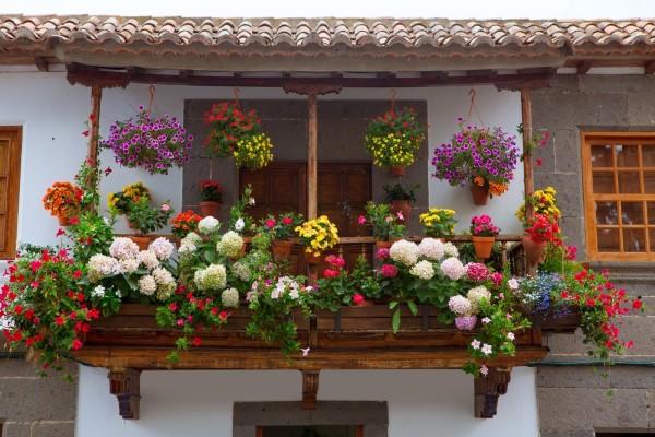 Balcón andaluz lleno de macetas con flores (España)