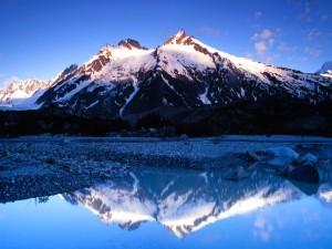 Cordillera reflejada en el agua azul