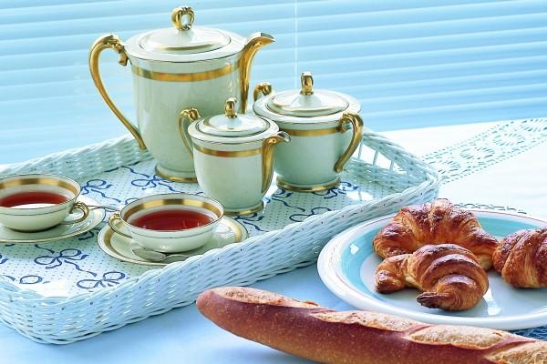 Desayuno con té, pan y cruasanes