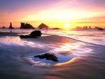 Amanecer en una playa de arena y rocas