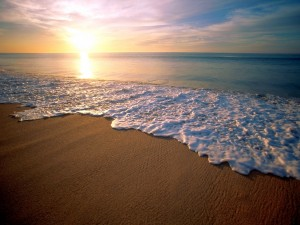 Postal: El agua del mar llegando a la orilla de la playa