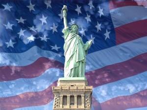 Postal: La Estatua de la Libertad con la bandera americana de fondo