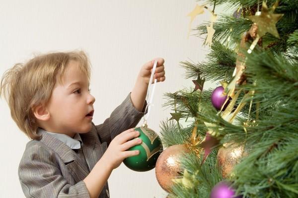 Un niño decorando el árbol de Navidad
