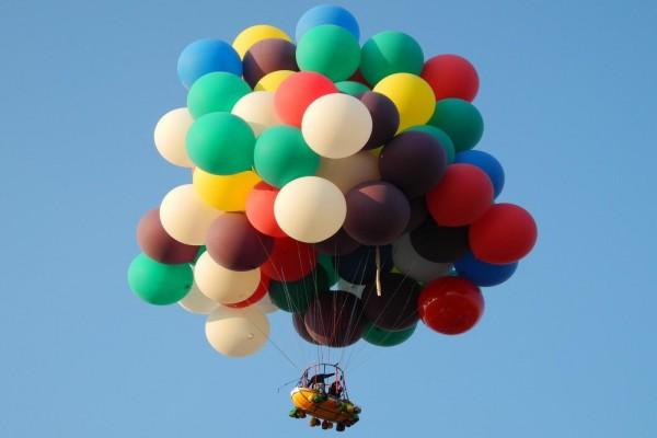 Volando con muchos globos de colores