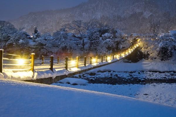 Puente iluminado cubierto de nieve