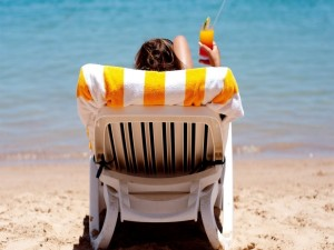 Sentada frente al mar tomando un cóctel