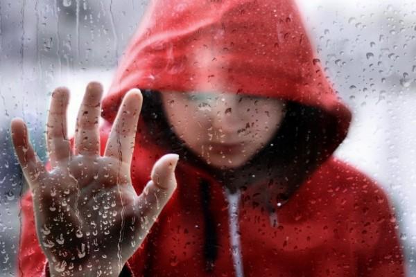 Apoyada en una ventana, bajo la lluvia