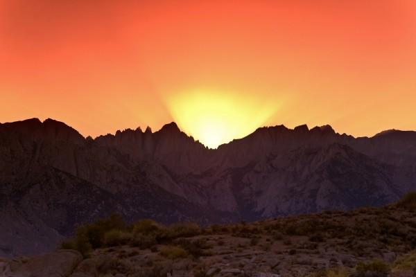 El sol iluminando un cielo anaranjado, en Alabama Hills (California)