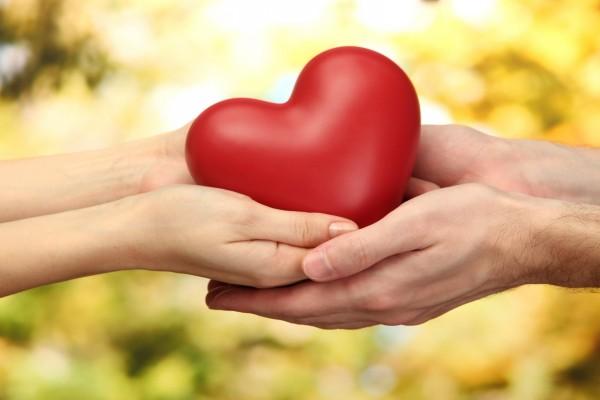Manos de una pareja sosteniendo un corazón