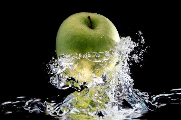 Manzana verde cayendo al agua
