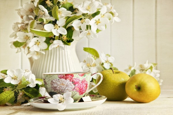 Taza de té, acompañada de flores de jazmín y manzanas verdes
